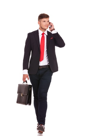 full length picture of a young business man holding a briefcase and walking forward while speaking on the phone and looking away from the camera. isolated on white background photo