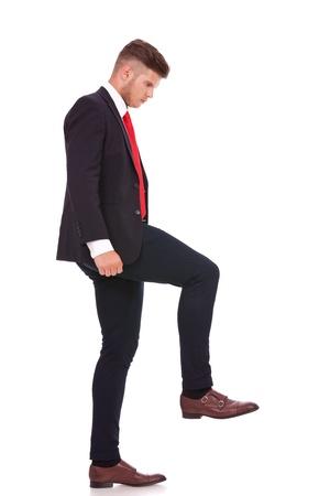 crush on: foto de cuerpo entero de un hombre de negocios joven que camina en algo imaginario y mirarlo. aislado en fondo blanco