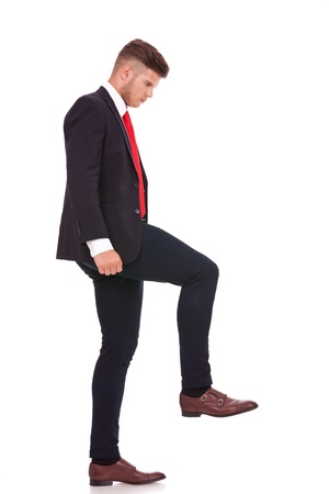 full length picture of a young business man stepping on something imaginary and looking at it. isolated on white background