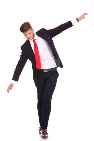 full length picture of a young business man balancing on an imaginary rope and looking down. isolated on white background photo