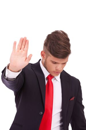 shut down: young business man showing you the talk to the hand gesture, stopping you from speaking while looking down. isolated on white background