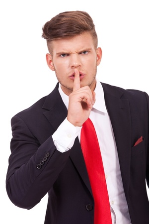 closeup portrait of a young business man telling you to keep the silence with a finger at the mouth gesture. isolated on white background photo