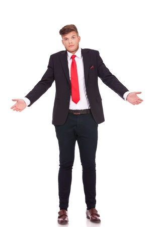 lack of confidence: young business man raising his shoulders, not knowing what to say with an expressive figure. isolated on white background