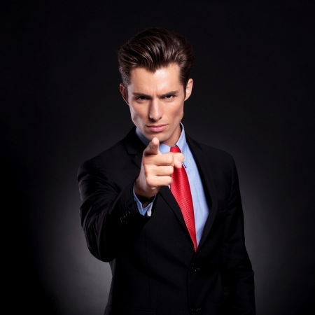 portrait of a young business man standing against a black background and pointing and looking at the camera with a threatening expression photo