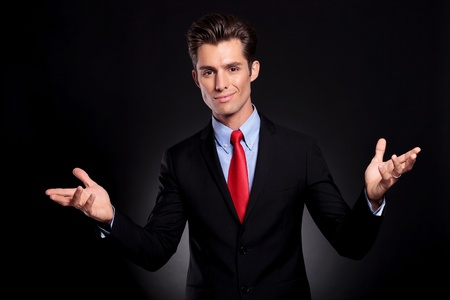 portrait of a young business man standing against a black background and welcoming you with his arms opened and a big smile on his face photo