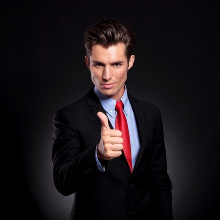 portrait of a young business man standing against a black background and showing thumbs up sign while looking at the camera photo