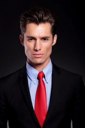 closeup portrait of a young business man standing against a black background and looking at the camera with seriousness photo
