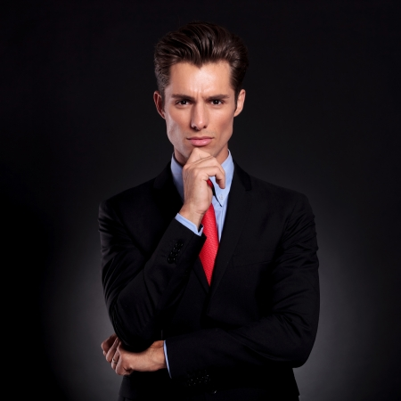portrait of a young business man standing against a black background with a pensive expression with his hand on his chin and looking at the camera photo