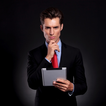 portrait of a young business man standing with his hand on his chin against a black background while holding a tablet and lookong pensively at the camera photo