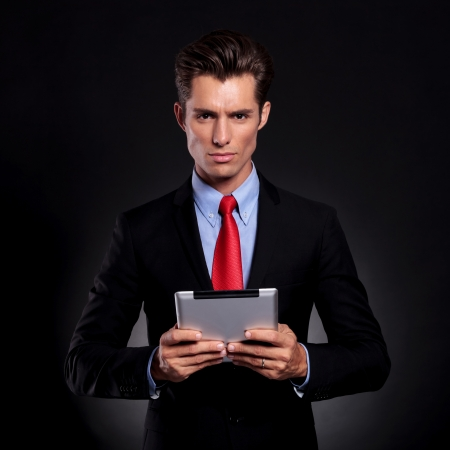 portrait of a young business man standing against a black background and holding a tablet with both his hands while looking at the camera with a serious expression photo