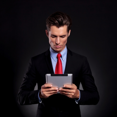 portrait of a young business man standing against a black background, holding and looking at a tablet photo