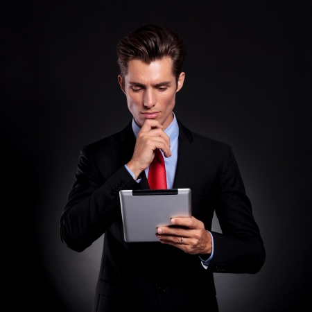 portrait of a young business man standing against a black background holding and looking at a tablet with a pensive expression and his hand on his chin photo