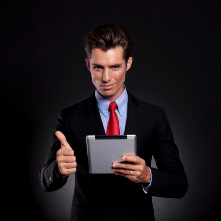 portrait of a young business man standing against a black background holding a tablet and showing the thumbs up sign while smiling to the camera photo
