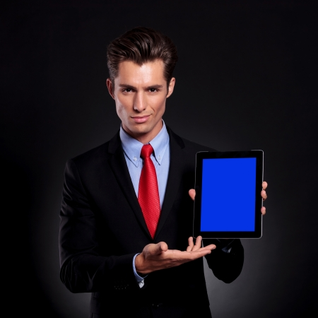 portrait of a young business man standing against a black background presenting a tablet with a faint smile on his face photo