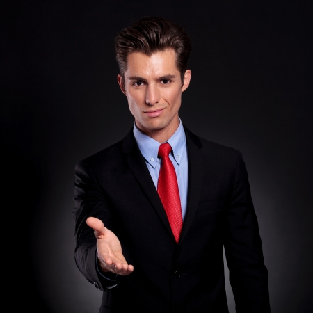 portrait of a young business man standing against a black background putting his hand out for a handshake while smiling to the camera photo