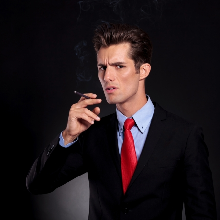 portrait of a young business man standing against a black background and preparing to take a smoke out of his cigarette while looking at the camera photo