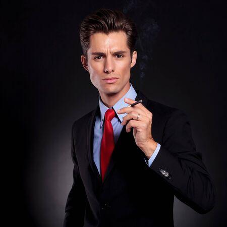 hombre fumando puro: retrato de un hombre de negocios de pie sobre un fondo negro con un cigarrillo en la mano y mirando a la cámara