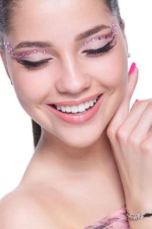 touch down: closeup of a beautiful young casual woman with diamond makeup looking down and touching her face while smiling Stock Photo