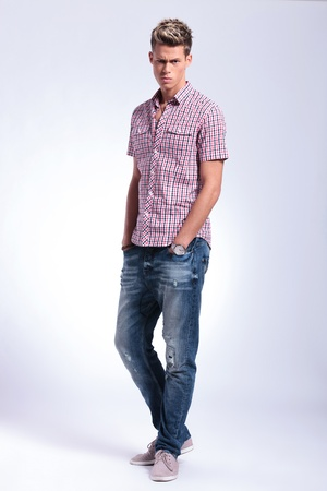 raised eyebrows: full length picture of a casual young man standing with his hands in his pockets and looking at the camera with a raised eyebrow. on gray background