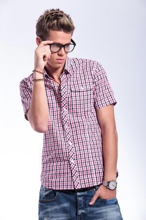 adjusting: casual young man adjusting his eyeglasses and holding a hand in his pocket while looking away from the camera. on background