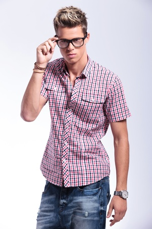 adjusting: casual young man holding his hand on his glasses and fixing them while looking at the camera. on gray background