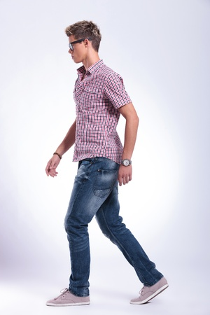 side view of a casual young man walking forward, away from the camera. on gray background photo