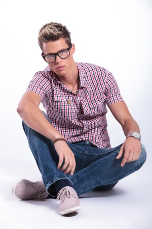 sitting on the ground: casual young man sitting on the floor with his legs crossed and holding his hands on his knees while looking at the camera. on background
