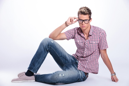 casual young man sitting on the floor and adjusting his eyeglasses while looking at the camera with serious expression. on background photo