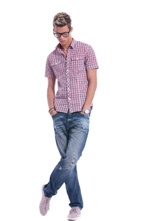 dissapointed: full length picture of a casual young man standing with his hands in his pockets, with his legs crossed, while looking down   on background