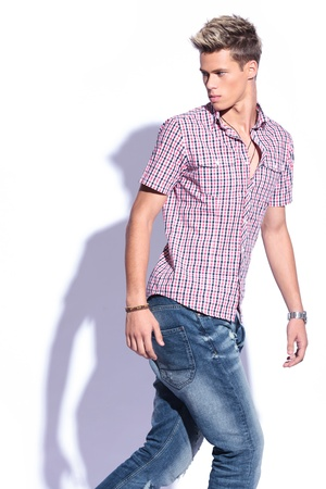 casual young man walking and looking back, away from the camera   on white background with shadow photo