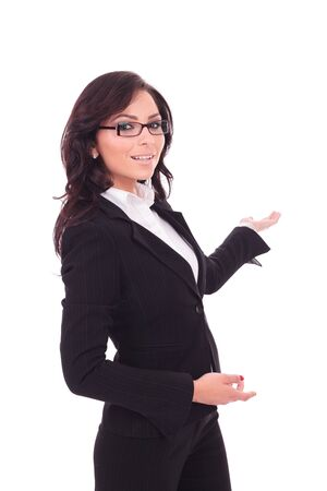 indicating: young business woman presenting something in the back while looking at the camera with a smile on her face. on white background