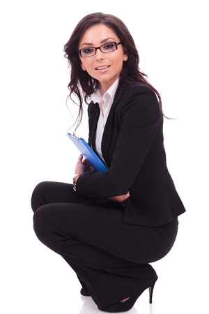 crouched: side view of a beautiful young business woman sitting crouched with her clipboard in her hands and looking at the camera. on white background Stock Photo