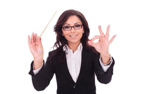 jeune femme d'affaires dirige avec une baguette et un sourire. sur fond blanc
