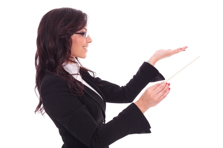 side view of a young business woman holding a conductors stick and conducting while looking away from the camera and smiling. on white background photo