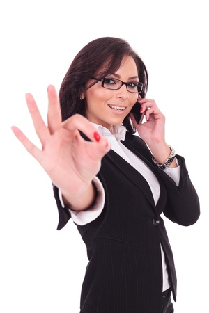 young business woman shows the ok sign while on the phone, smiling at the camera. on white background photo