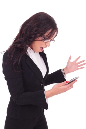 business woman standing: young business woman looking at her phone and acting angry. on white background Stock Photo