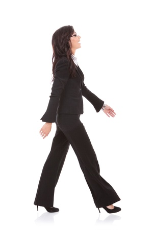 side view of a young business woman walking forward and laughing. on white background photo