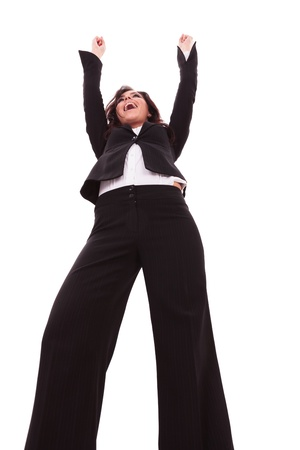 low angle view of a young business woman screaming of joy with her hands in the air, while looking away. on white background