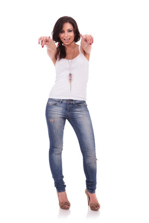 indicating: full length picture of a casual young woman  pointing with both her hands towards the camera, while smiling. on white background Stock Photo
