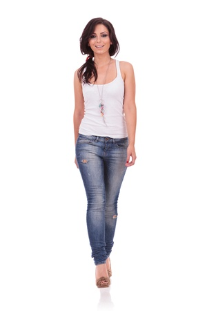 toward: full length picture of a casual young woman walking straight toward the camera with a smile on her face. on white background