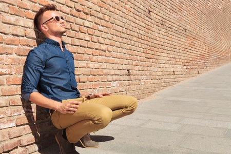 crouched: casual young man sitting in a crouched position with his back by a brick wall and looking away from the camera
