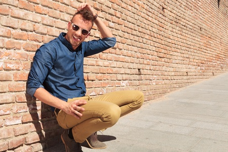 crouched: casual young man goofing around while sitting crouched by a brick wall, scratching his head and pulling his tongue out, while looking at the camera Stock Photo