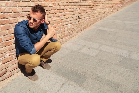 to crouch: casual young man crouching by a brick wall and holding a hand with the other which is on the back of his head while looking away from the camera