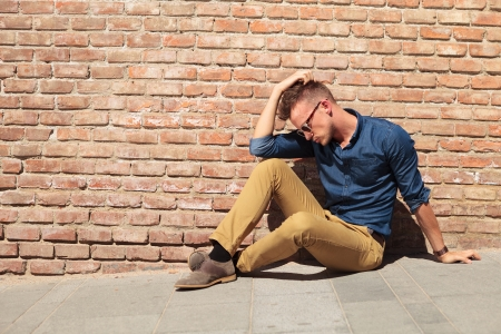 dissapointed: casual young man sitting on the sidewalk next to a brick wall with his hand on his head and looking down Stock Photo