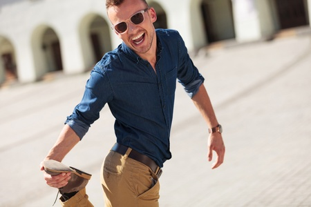casual young man goofing around, holding his foot and smiling to the camera photo