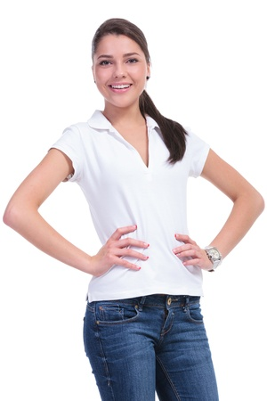 casual young woman standing with her hands on her hips, facing the camera and smiling . isolated on white background photo