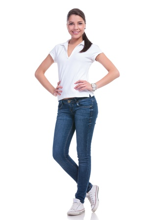 full length: full length picture of a casual young woman standing with her hands on her hips and smiling to the camera. isolated on white background