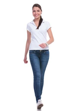 caminando: mujer joven casual caminando a la c�mara con una sonrisa. aislado en fondo blanco Foto de archivo