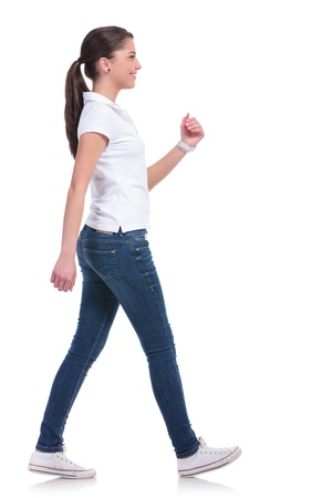 walking away: side view of a casual young woman walking away from the camera and smiling. isolated on white background