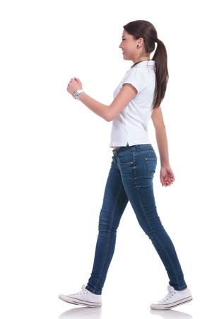 Seitenansicht einer jungen Casual Frau zu Fuß und wir freuen uns. isoliert auf weißem Hintergrund